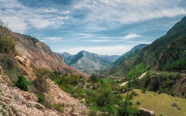 Потрясающий панорамный вид с перевала в горную долину при солнечном свете