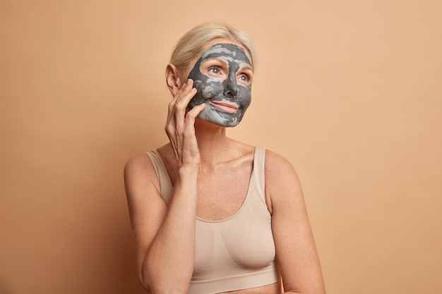 Awesome relaxed woman applies clay mask on face touches cheek and looks with dreamy expression has natural beauty undergoes cosmetic procedures dressed in cropped top isolated on beige wall