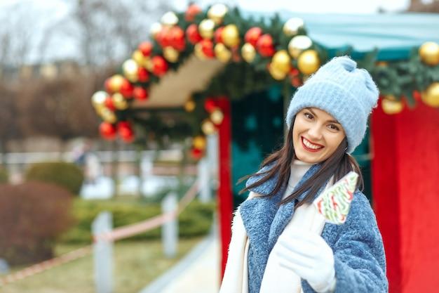クリスマスマーケットでキャンディーを保持している素晴らしい笑顔の女性。空きスペース
