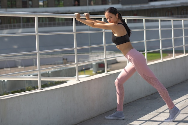 Awesome tanned athletic woman wearing sport apparel doing workout at the stadium. space for text