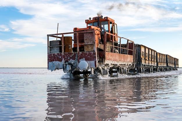 美しい青い空を背景に白い塩で水の中のレールに素晴らしい列車が乗っています。