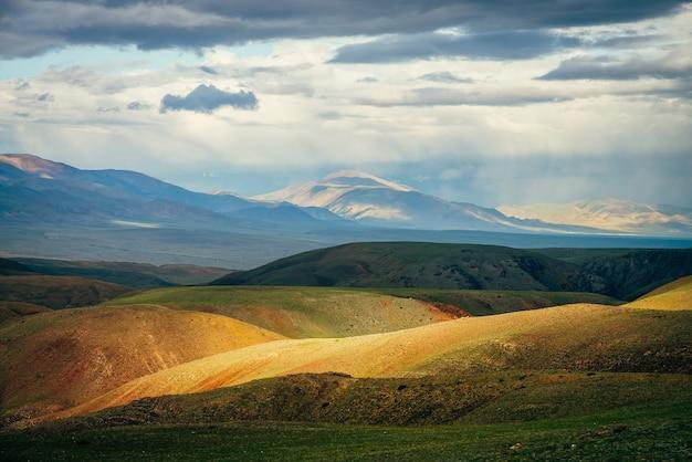 일몰에 생생한 여러 가지 빛깔의 산이있는 멋진 광활한 풍경.