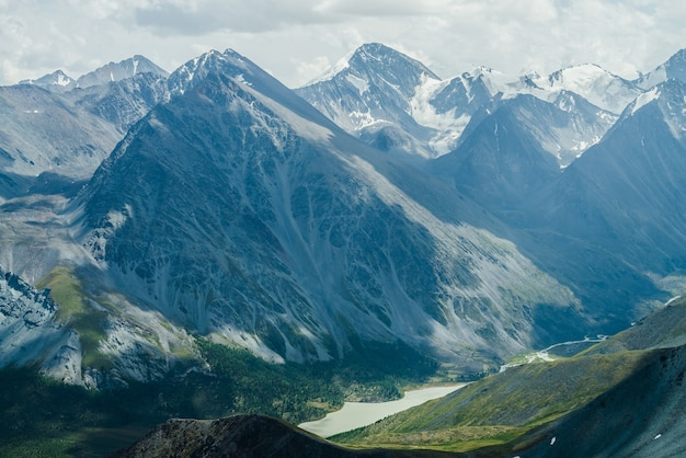 Awesome view to mountain valley with lake and huge glacier mountains under gray cloudy sky.