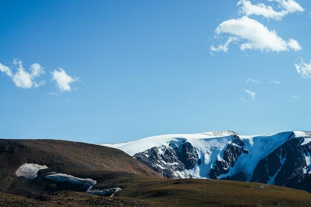 Потрясающий вид на большие заснеженные горы за зеленым холмом.