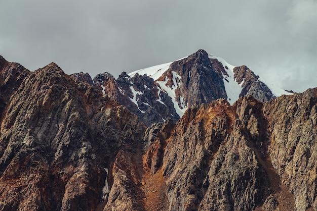 흐린 하늘 아래에 날카로운 돌이있는 아름다운 산 뒤에 큰 뾰족한 바위에 거대한 빙하에 대한 멋진 전망. 흐린 날에 큰 뾰족한 바위 산이있는 대기의 고원 풍경