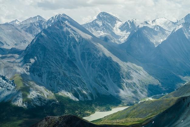 Потрясающий вид на горную долину с озером и огромными ледниковыми горами под серым облачным небом.