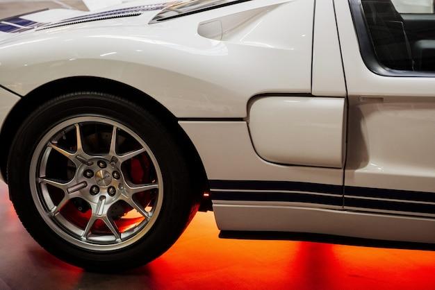 Потрясающий белый спортивный автомобиль с синими линиями и желтыми неоновыми огнями внизу