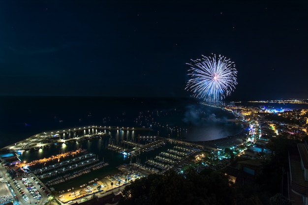 Awesome wide angle shot of fireworks above the blanes in catalonia, spain