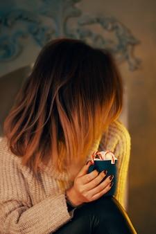 Потрясающая женщина в свитере с чашкой кофе у камина кружкой горячего шоколада с зефиром ...
