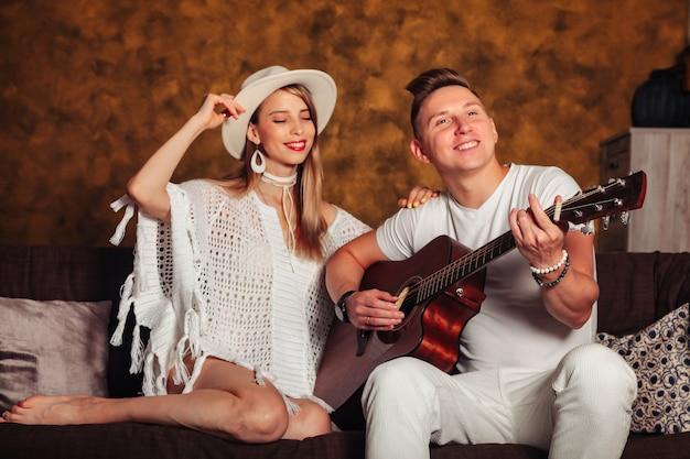 Потрясающий молодой мужчина и женщина в белой одежде с гитарой в интерьере гостиной. пара на софе с гитарой. концепция домашнего обучения или музыкальной игры дома и музыкального образования. копировать пространство