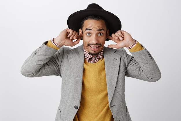 Awkward african-american man shut ears and looking confused, can't hear anything at loud place