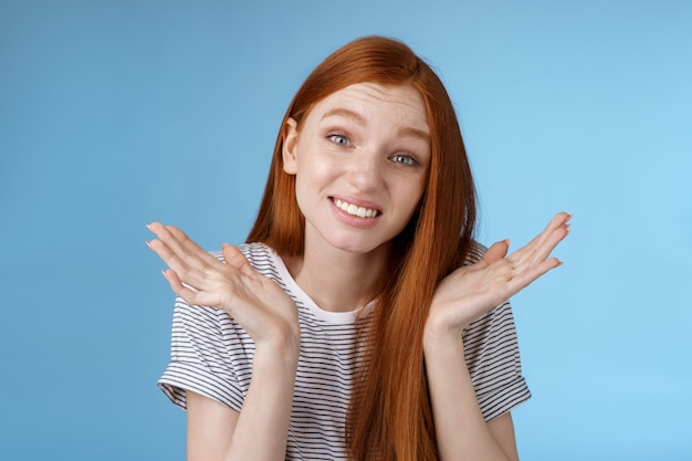 Awkward apologizing cute redhead girlfriend say sorry shrugging spread hands sideways puzzled smiling uncomfortably standing clueless unaware forgetting meeting, posing blue background.