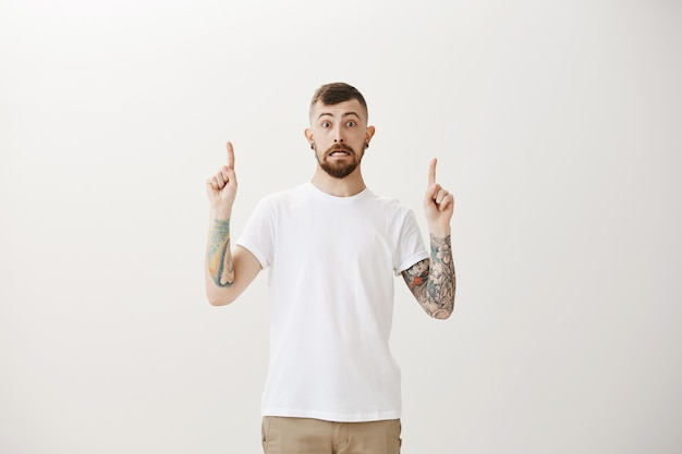 Awkward and astounded hipster guy looking startled and pointing fingers up