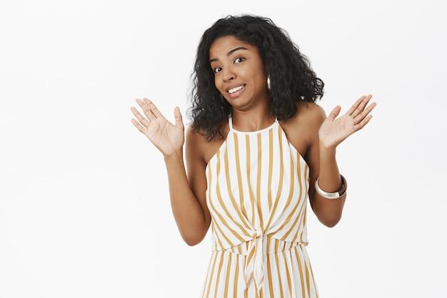 ぎこちない不機嫌な変な浅黒い肌の女性が降伏して手のひらを上げ、偽の笑顔で笑って肩をすくめる