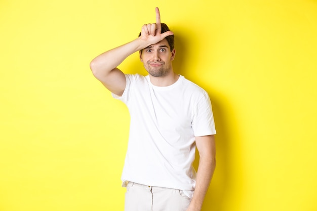 Awkward guy showing loser sign on forehead, looking sad and gloomy, standing in white t-shirt against yellow background.