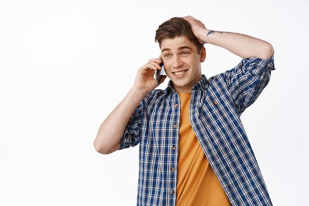 ぎこちない男が携帯電話で話し、誰かに電話をかけ、躊躇しているように見え、頭に触れて優柔不断に脇を見て、何を言うべきかわからない、白の上に立っている
