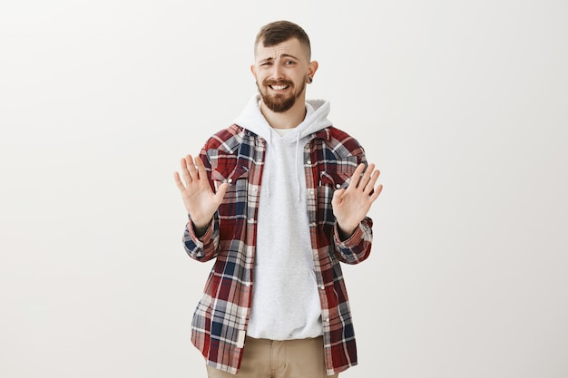 Awkward hipster guy rejecting offer, shaking hands in refusal and making forced smile