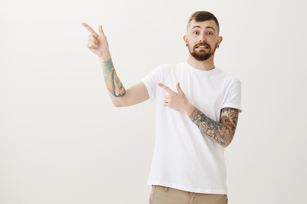 Awkward and indecisive handsome guy pointing left and worried