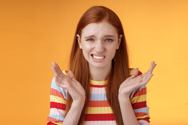 Awkward unhappy worried young redhead girl cringe feel sorry apologizing smirking smiling nervously frowning squinting spread hands sideways shrugging confused, standing orange background.