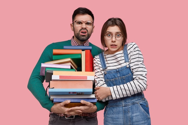 Awkward unshaven young man frowns face, wears big square spectacles, carries many textbooks, young european woman keeps hands crossed over chest