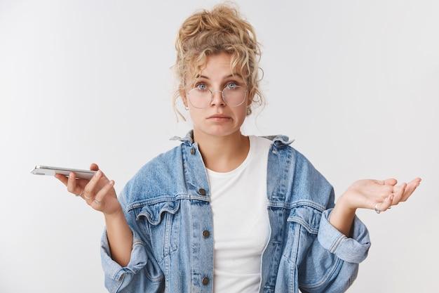 Неуклюжая неуверенная невежественная милая неуклюжая европейская блондинка-помощница в очках грязная булочка ухмыляется неуверенно разводит руки в стороны, не подозревая, что держит смартфон, не уверен, как решить проблему