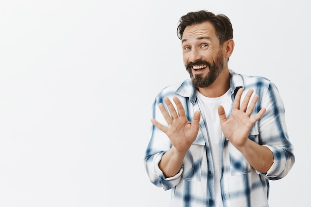 Uomo maturo barbuto imbarazzante e preoccupato in posa