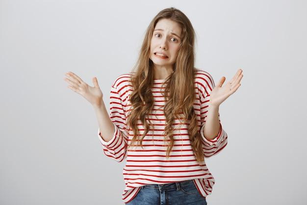 Неловко взволнованная девушка извиняется, поднимая руки невежественно