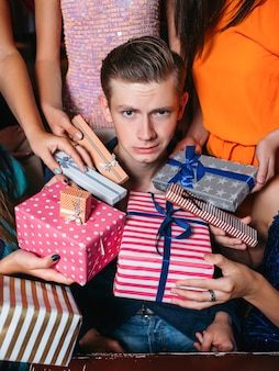 Awkward young male at christmas party. many females attention, new year colorful gifts. tired man, unrecognizable girls, comfortless, spoiled child concept