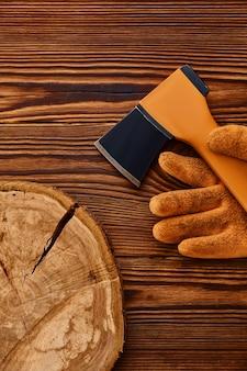 나무 테이블에 도끼와 장갑. 전문 도구, 목수 장비, 목공 도구
