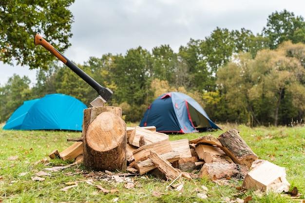 Топор и куча дров для костра. палатки на фоне. концепция кемпинга