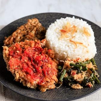 Ayam geprek은 인도네시아에서 인기 있는 길거리 음식입니다. 삼발 바왕(고추 마늘 소스)에 으깬 바삭한 치킨으로 만듭니다. 쌀과 야채와 함께 제공