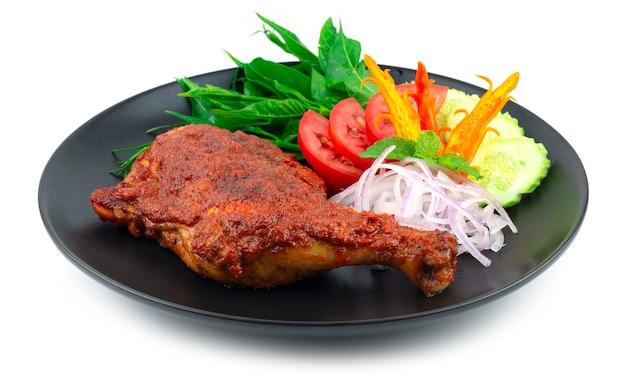 Ayam golek 구운 치킨 드럼스틱 코코넛 크림 소스 멜라유 스타일 블랙 플레이트 장식 양파 슬라이스 및 야채 사이드뷰에 인기 있는 태국 남부