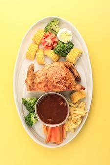 Ayam kodok setengah, целая курица, фаршированная наполовину, с мясом внутри. подается с тушеными овощами и грибным соусом на желтом фоне