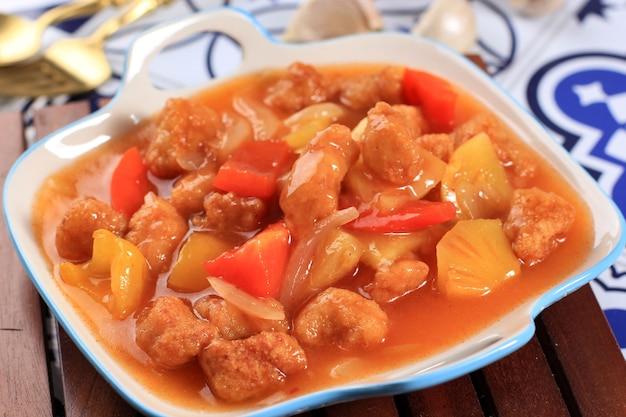 Ayam kuluyuk 또는 ayam goreng saus asam manis, 새콤한 소스를 곁들인 프라이드 치킨, 화이트 림 블루 플레이트에 제공되는 중국 인도네시아 요리.