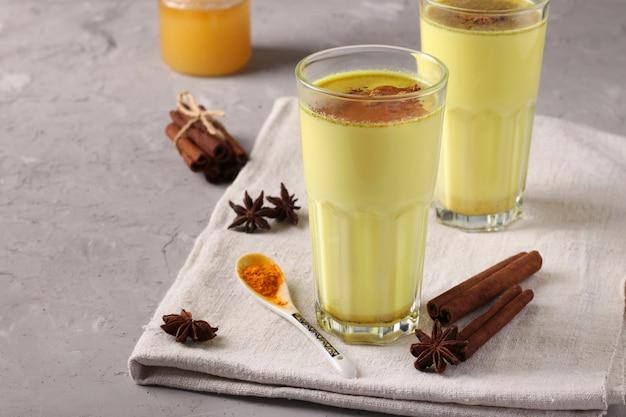 Аюрведический молочный латте с золотой куркумой в стакане с куркумой, звездой корицы и аниса
