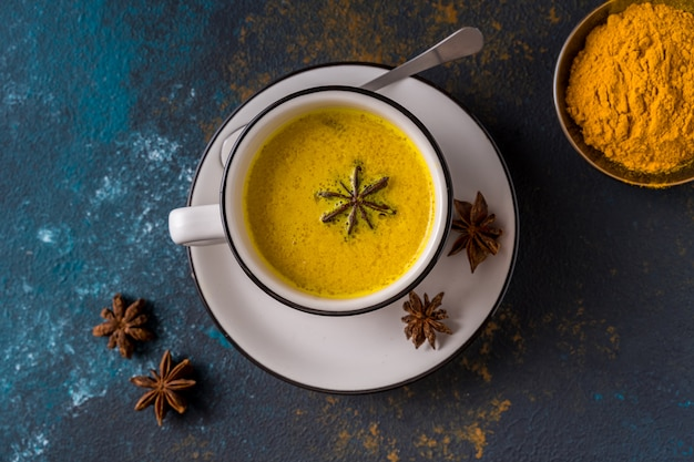 Ayurvedic golden turmeric latte milk made with turmeric and other spices on blue table