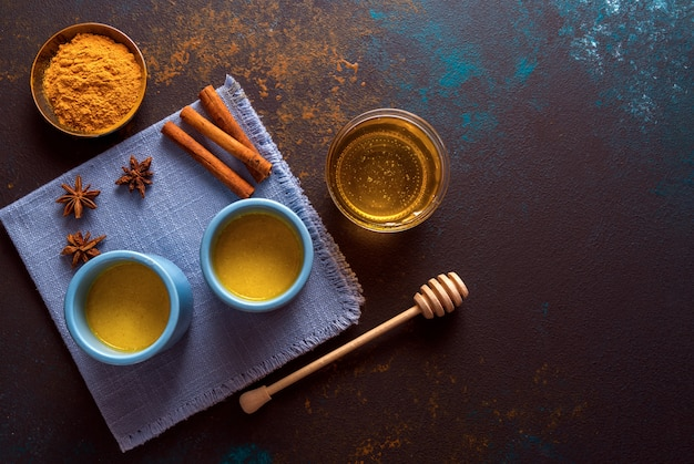 Ayurvedic golden turmeric latte milk made with turmeric and other spices on wooden background.