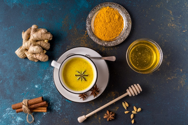 Ayurvedic golden turmeric latte milk made with turmeric and other spiceson blue