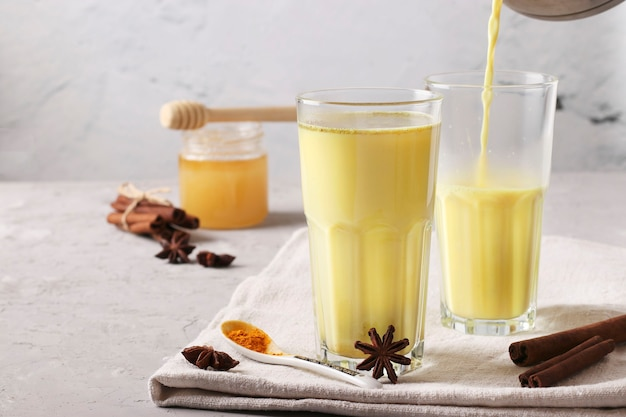 Ayurvedic golden turmeric latte milk in two glasses with curcuma powder, cinnamon and anise star on gray concrete background, closeup, place for text
