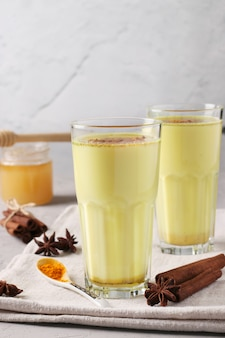 Ayurvedic golden turmeric latte milk in two glasses with curcuma powder, cinnamon and anise star on gray concrete surface, vertical format