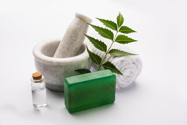 Аюрведическое мыло для ванн с нимом, состоящее из azadirachta indica, с листьями, строительным раствором, полотенцем и эфирным маслом. выборочный фокус