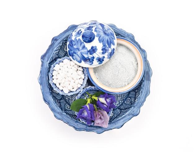 アーユルヴェーダの香りのパウダーとバタフライピーフラワーが顔と体にペイントされ、スキンケア用に白で隔離されています。上面図、フラットレイ。