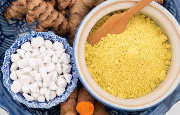 白で隔離されたスキンケアのために顔と体に塗るためのターメリックとアーユルヴェーダの香料入りパウダー。