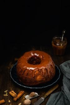 暗い木製のテーブルにスパイス、シナモン、スターアニス、ナツメグ、キャラメルソースのaze薬と外undケーキ