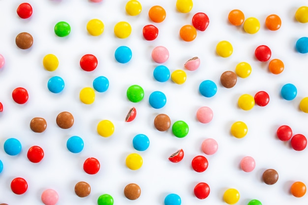 散らばったマルチカラーの小さな丸いキャンディー。白地にマルチカラーのaze薬でチョコレートの糖衣錠