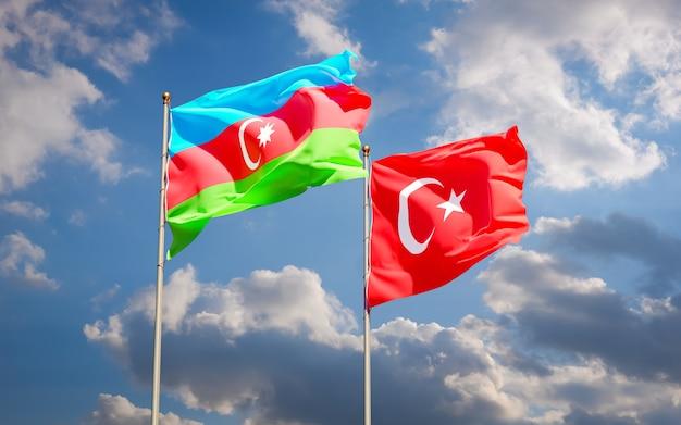 青い空に手を振っているアゼルバイジャンとトルコの旗。