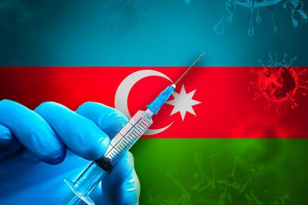 아제르바이잔 covid19 예방 접종 캠페인 파란색 고무 장갑을 끼고 깃발 앞에 주사기를 들고 있습니다