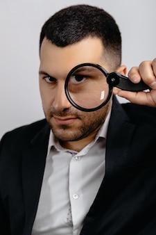 양복을 입은 아제르바이잔 남자가 한 눈으로 돋보기를 통해 본다.