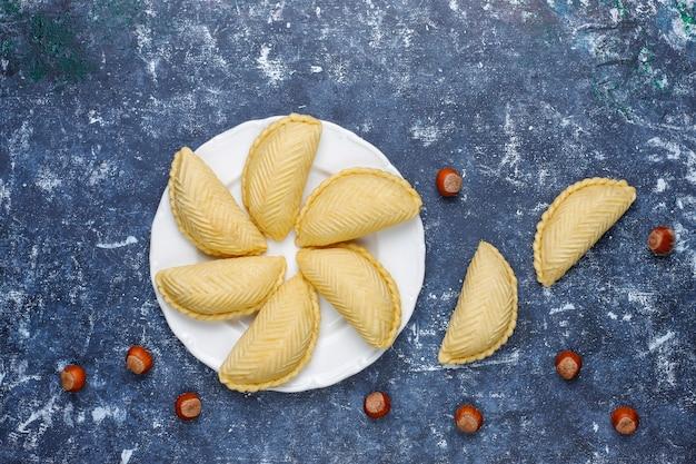 Азербайджанская национальная выпечка шакарбура на белой тарелке, вид сверху, весенний новогодний праздник, праздник новруз.