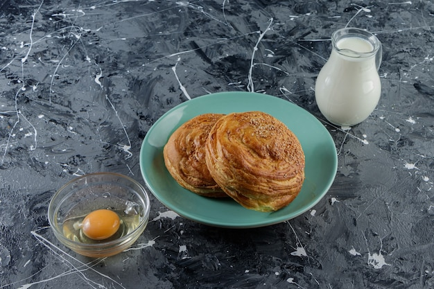 Pasticceria nazionale dell'azerbaigian con uovo di gallina crudo e una brocca di vetro di latte fresco.